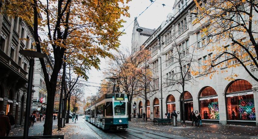 Travía pasando por calle en ciudad suiza.